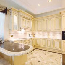 The Kitchens - Palladio 2 - Evoluzione della Palladio Kitchen in finitura laccata avorio patinato con particolari in foglia oro anticato. Penisola con piano in marmo bicolore. Marmi utilizzati Travertino Doré ed Eramosa.